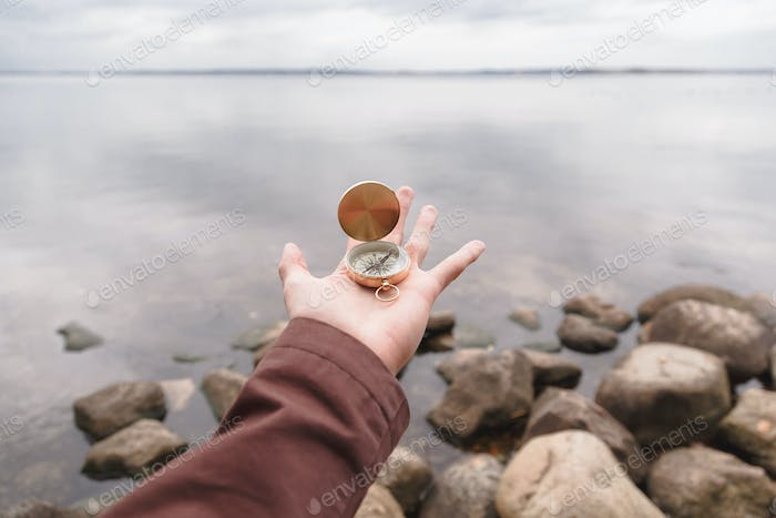 A traveler man holds a compass in his hand, standing on a stone beach. First person look