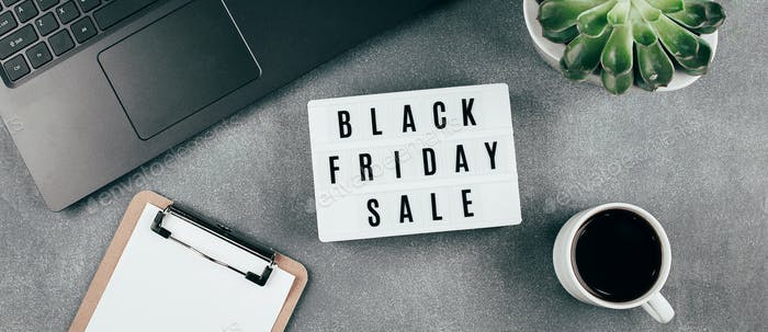 Black friday sale word on lightbox, laptop, coffee, empty blank, succulent plant on table. Banner