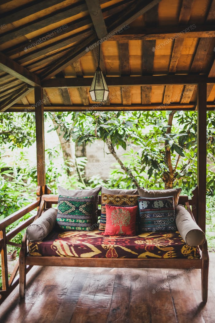 Wooden sofa with pillows on terrace under roof in ethnic style with colorful traditional ornaments