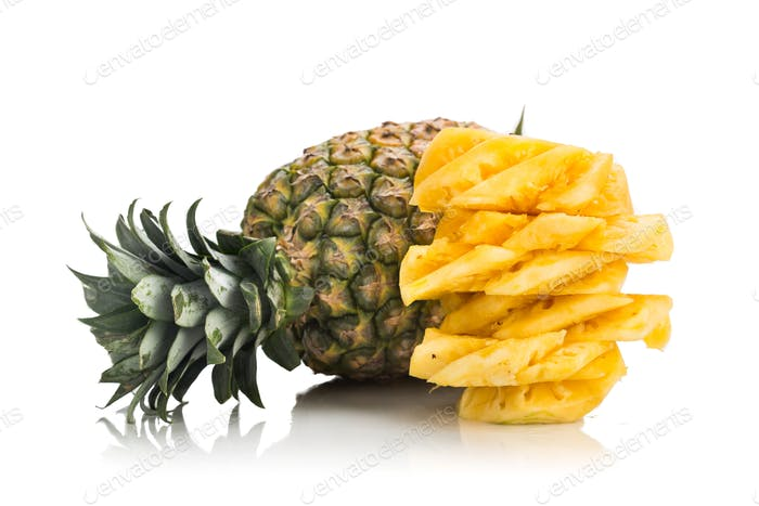 Fresh juicy nutritious cut pineapple with whole fruit as backgro
