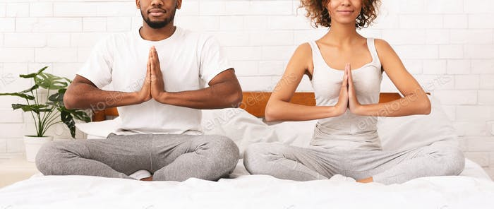Young black family meditating in bed together