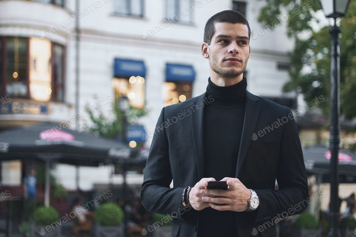 Businessman holding mobile phone and looking at it outdoors