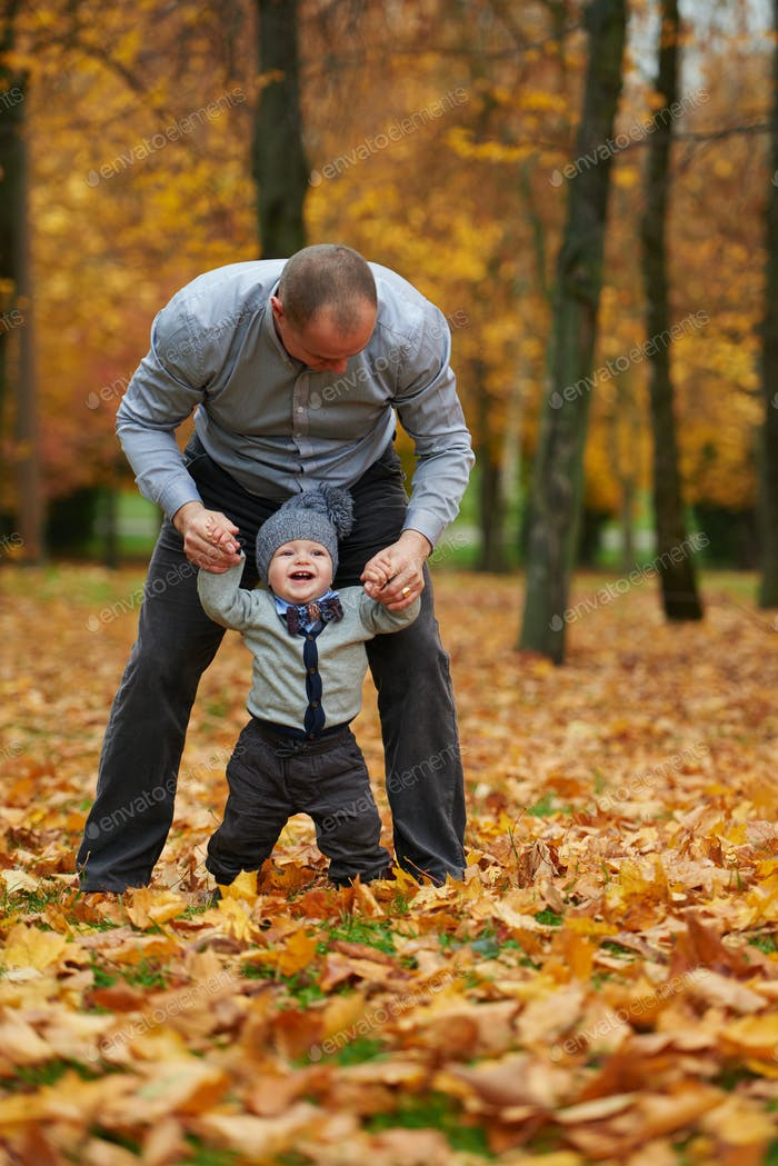 father with son walking in autumn forest