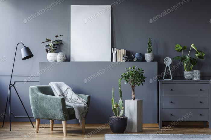 Green armchair between black lamp and plants in grey flat interi