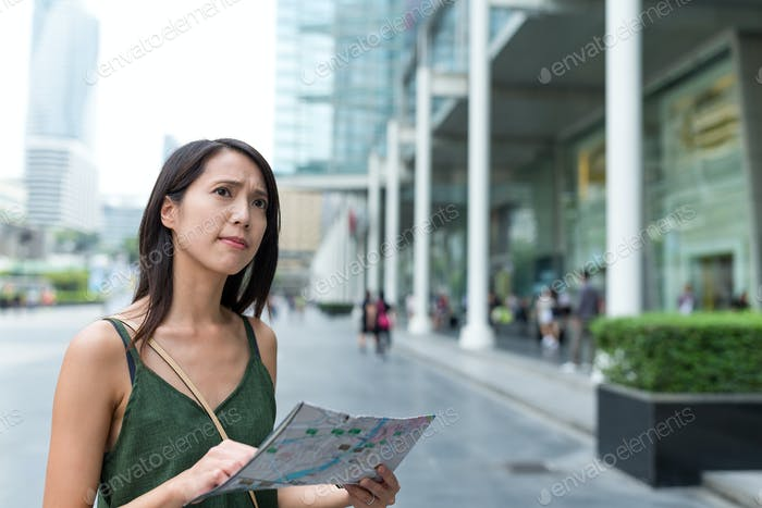 Woman finding the location on city map
