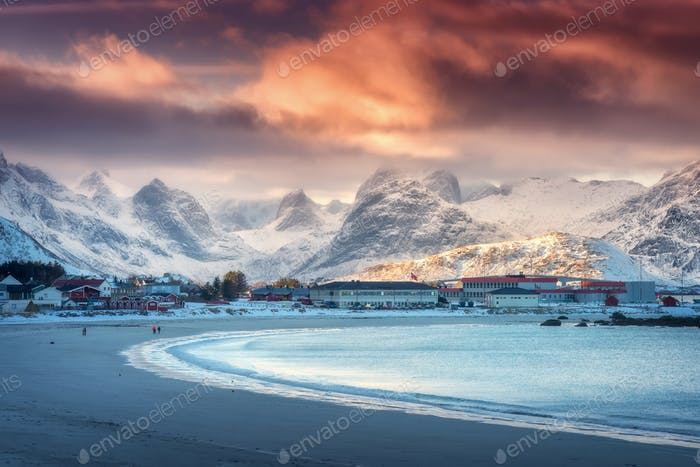 Beautiful arctic sandy beach, sea and snowy mountains at sunset