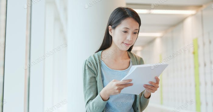 Woman reading on note at school