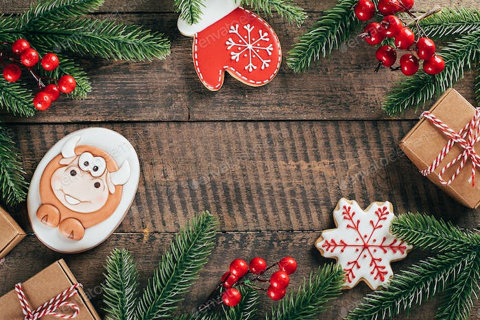 Christmas background with Gingerbread bull, mitten, snowflake, fir branch on wooden background.