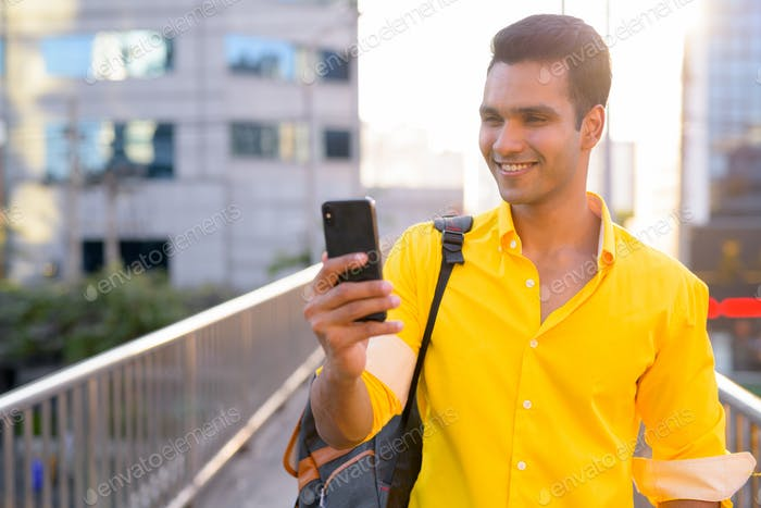 Happy young Indian man with backpack using phone on the footbridge