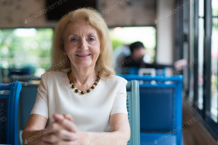 Portrait of happy senior woman smiling and looking at camera while sitting at restaurant