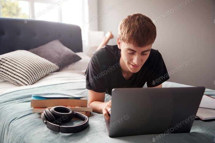 männlich college student liegt auf Bett in shared house arbeiten auf laptop