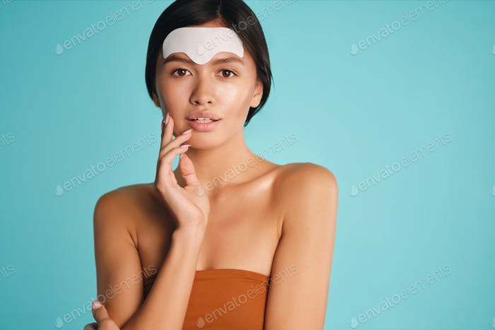 Beautiful tender Asian brunette girl applying facial mask dreamily looking in camera