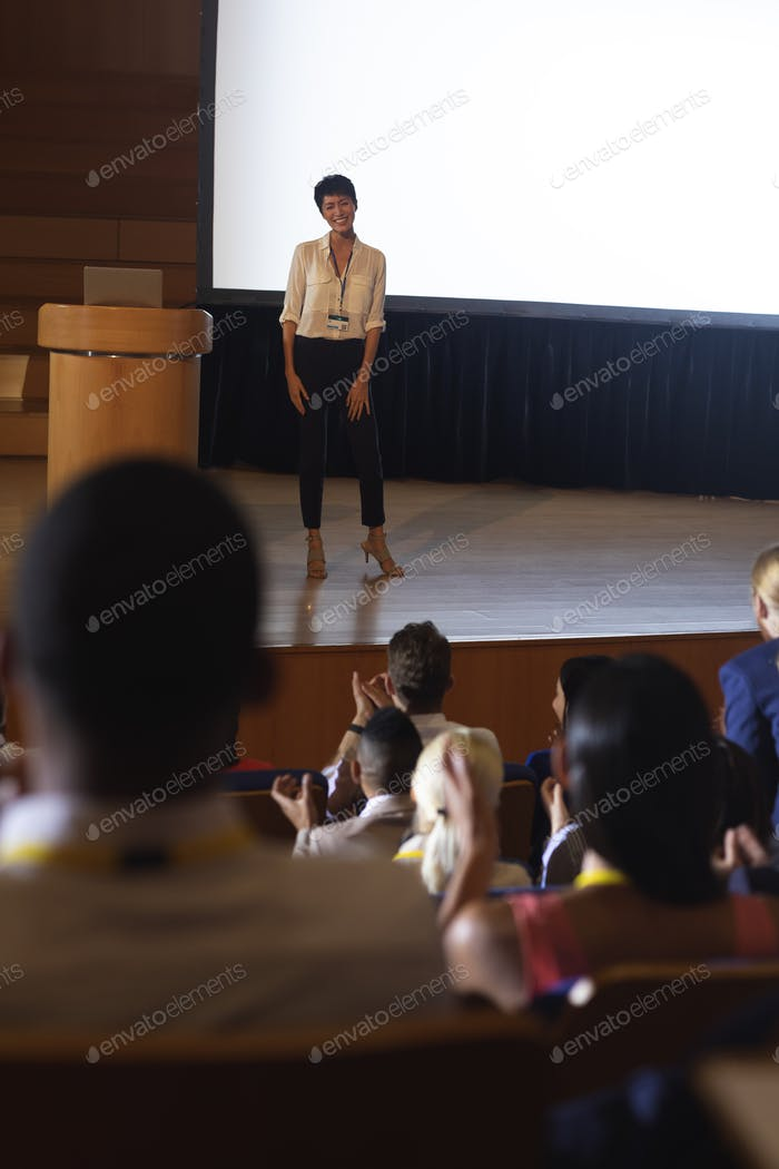 Beautiful businesswoman standing and giving presentation in front of the audience in auditorium