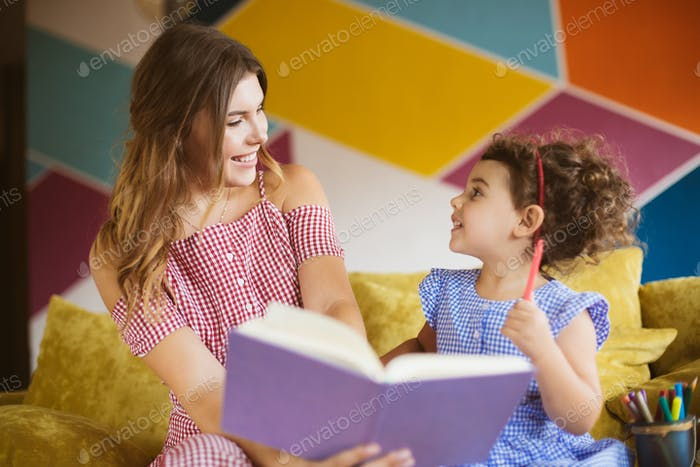 Beautiful smiling mother with her little cute daughter happily l