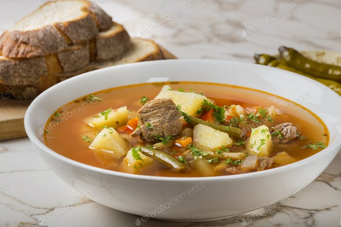 Bowl of vegetable beef soup with sliced bread and hot chilli peppers