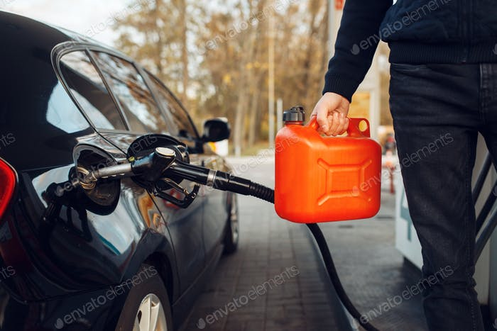 Man holding canister on gas station, fuel filling