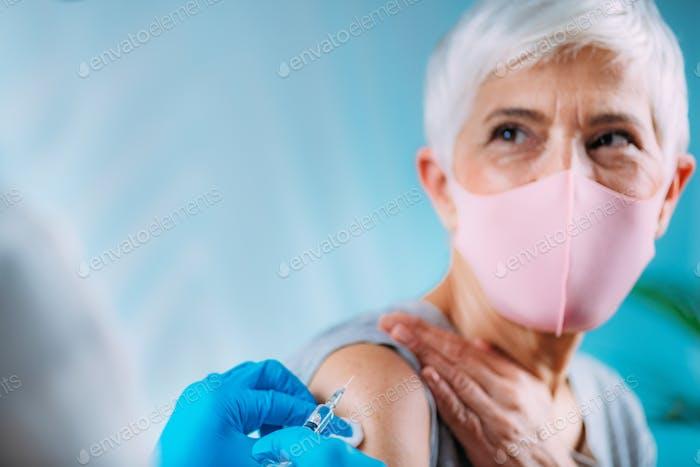 Hands of a nurse, holding a syringe with coronavirus vaccine.