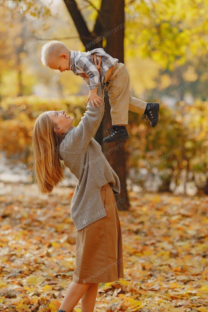Mutter mit kleinen Sohn spielen in einem Herbstfeld