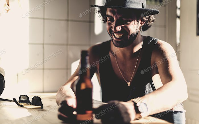 Bearded man wearing hat sitting indoors at a table, beer bottle in foreground.