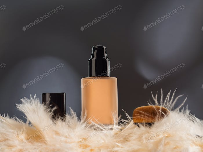 Unbranded generic foundation bottle with feathers and brush on gray background