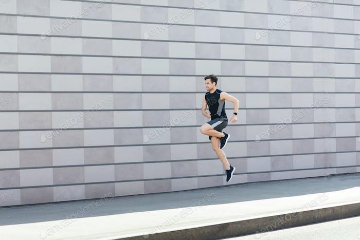 Замораживание в воздухе на тренировках. Стройный парень прыгает и бегает по улице