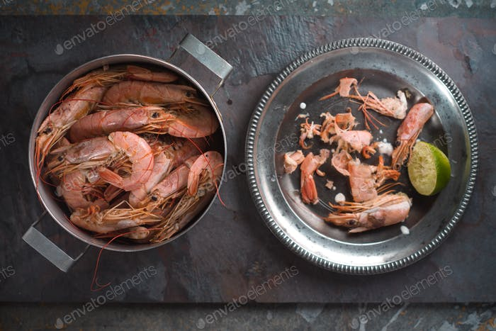 Pan with shrimps and a plate with shells from shrimps