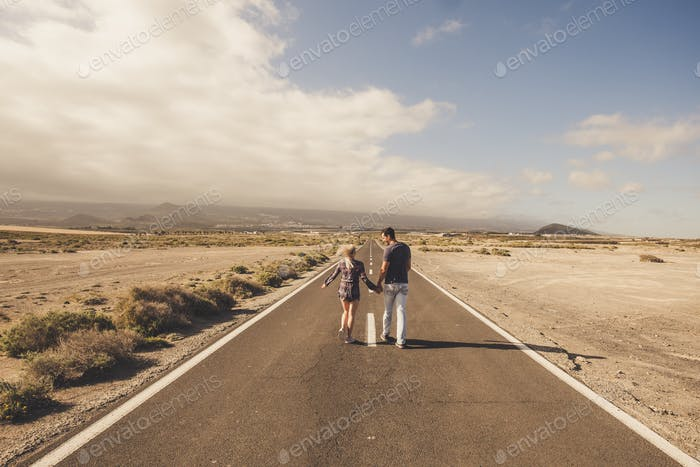Young couple walk together on a long straight road