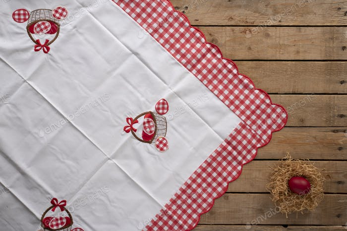 Easter tablecloth on a wooden surface with a nest and a red painted egg