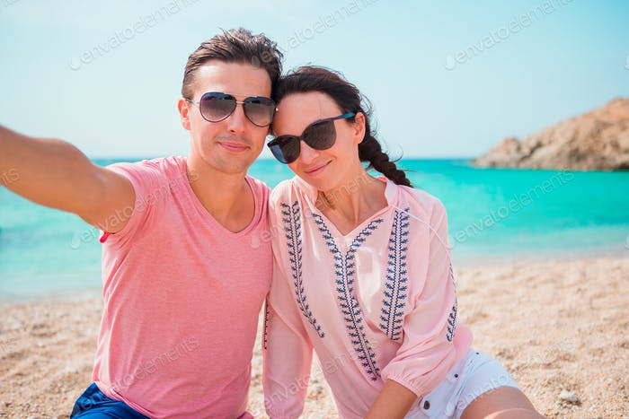 Selfie couple taking pictures on the beach in Cyclades. Tourists people taking travel photos with