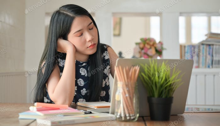 Thumbnail for A university student woman sat and closed her eyes while studying online at home.