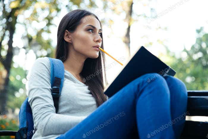 Female student sitting on the bench with book