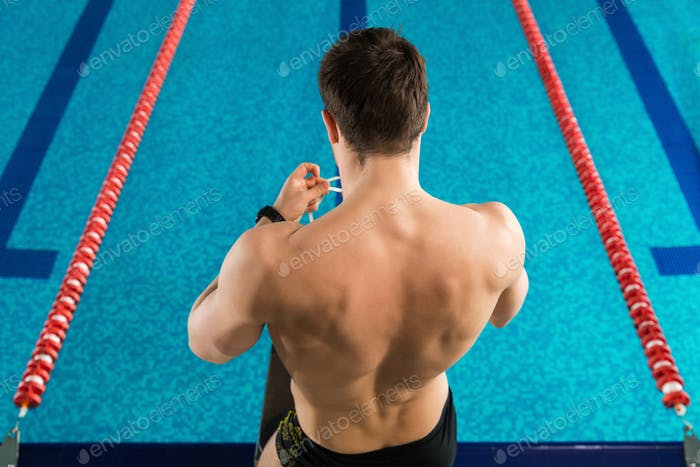 Rear view of a man preparing swimming goggles