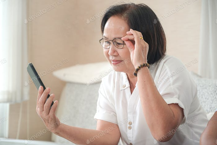 Elderly asian woman sitting on sofa is calling a video call on smartphone.