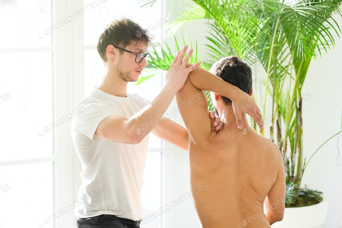Osteopath doing a shoulder evaluation on a man