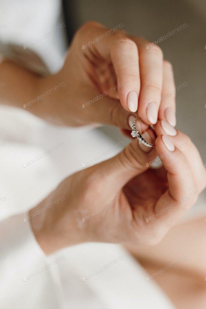 Die Braut hält einen Verlobungsring mit Edelsteinen