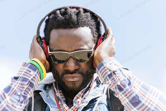 Afrikanischer junger Mann Musik hören.