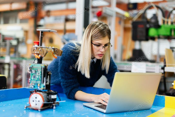 Young beautiful female engineer testing and programming