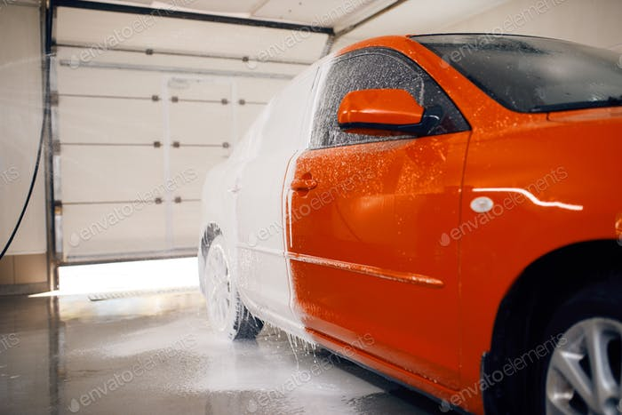 Automobile is half in foam, car wash service