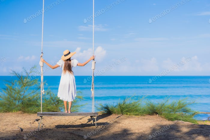 Portrait beautiful young asian woman relax smile on swing around beach sea ocean