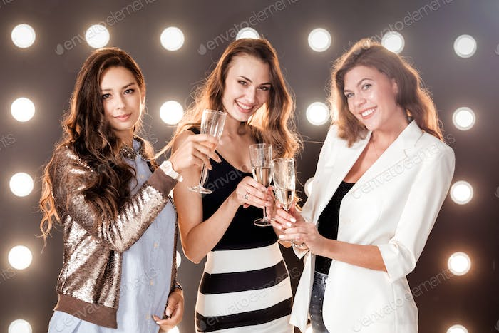 Three beautiful girls with glasses of champagne in hand smiling on the background wall with lights