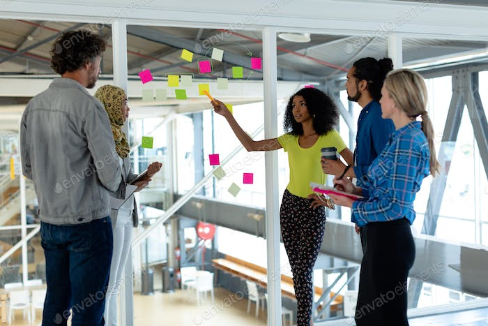 Side view of diverse business people discussing over sticky notes on glass wall in a modern office