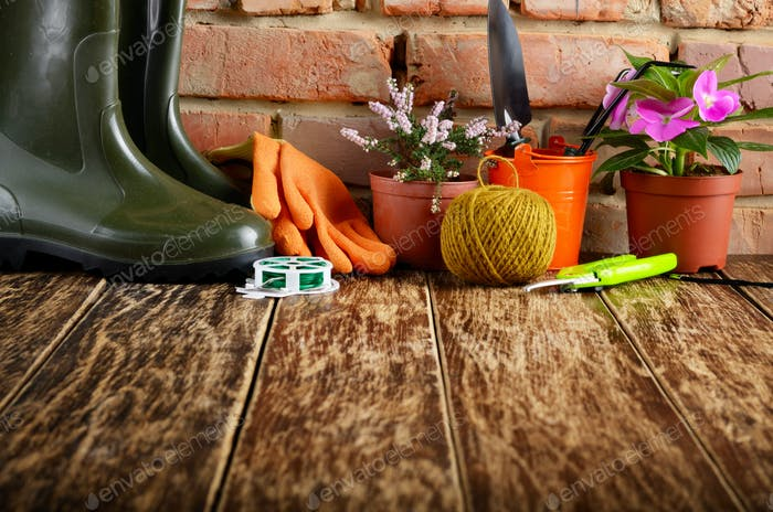 Gardening tools of shovel rake rope gloves on wooden floor