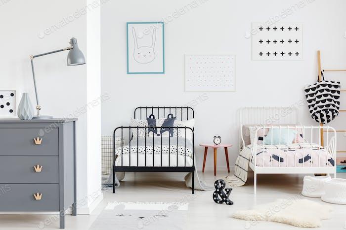 Graue Lampe auf Schrank im Kinderschlafzimmer Interieur mit Plakaten a
