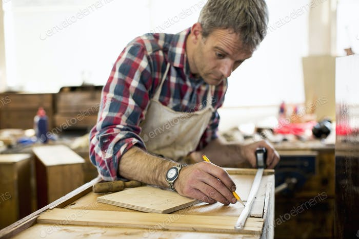 Un restaurador de muebles antiguos que mide una pieza de madera.