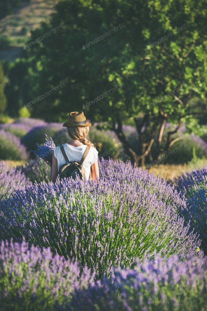 Young woman with backpack standing in lavender field, Isparta, Turkey