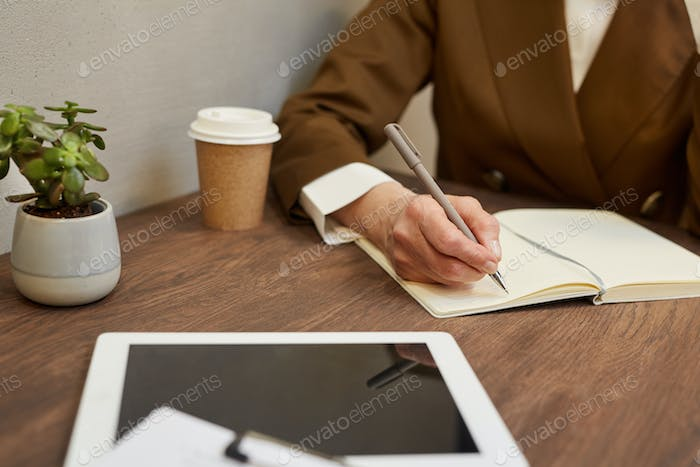 Mature Businesswoman Writing in Planner