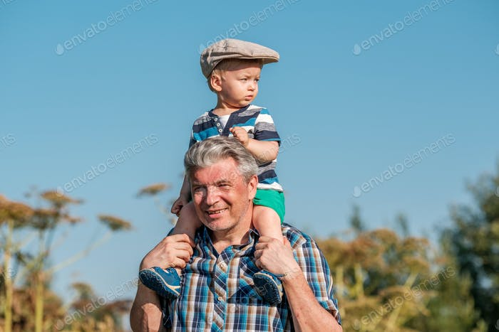 Grandfather carries grandson toddler boy on his shoulders