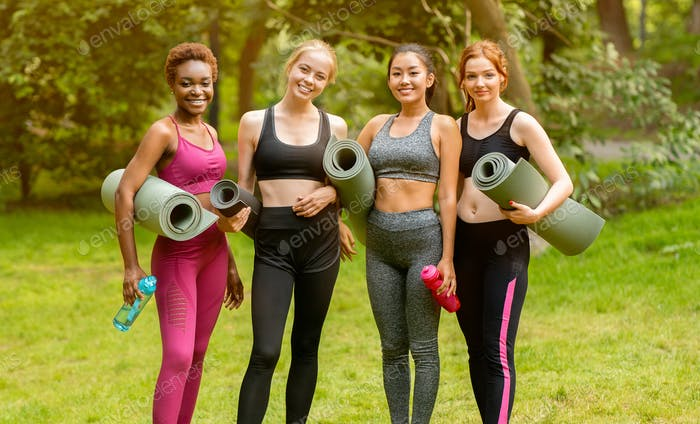 Cheerful young ladies in fitness outfits standing at park after yoga practice