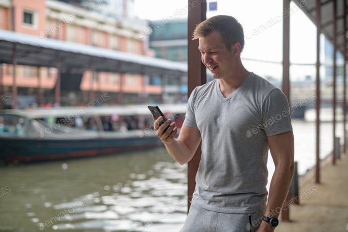 Young happy tourist man smiling while using phone at the local pier in Bangkok