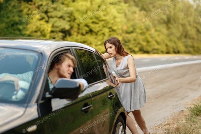 Young woman pushing broken car with man on road